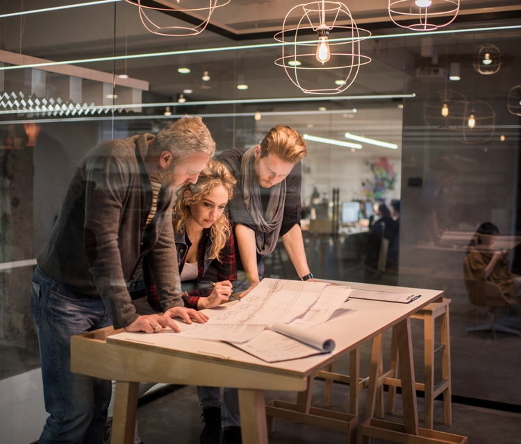 Group of creative people having a meeting in the office and working on blueprints. The view is through the glass.